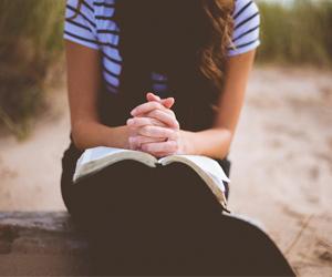 jeune fille qui prie les mains croisées