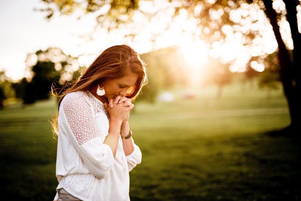 jeune femme qui prie au milieu de la nature