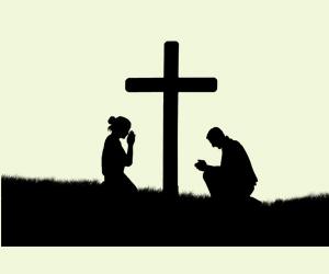 2 personnes prient autour de la croix
